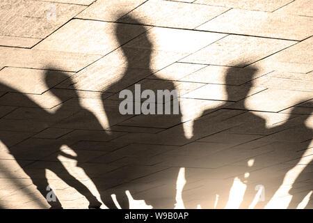 Les gens, des ombres et des silhouettes de personnes sur le trottoir, trottoir en matin lumineux, comme arrière-plan ou de texture, concept photo Banque D'Images