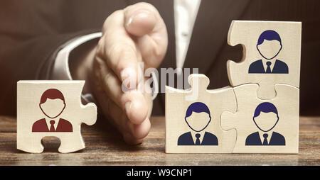 Le chef sépare le puzzle avec l'image de l'employé. Le concept de la gestion du personnel dans l'entreprise. Rejetant un employés d'un plateau Banque D'Images