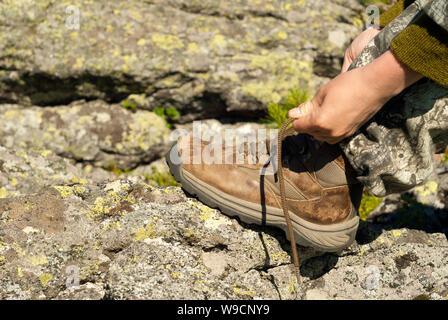 Lier les mains sur un lacet de démarrage randonnées usés close-up