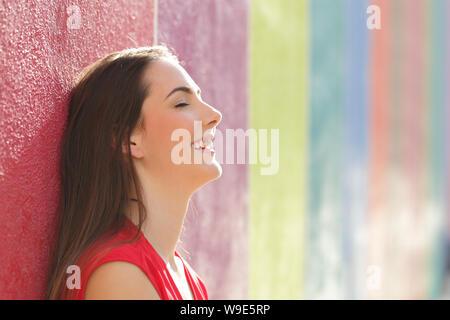 Vue de côté portrait of a happy woman leaning dans un mur coloré