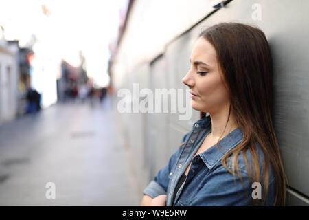 Vue latérale d'un triste portrait girl alone se plaindre s'appuyant sur un mur dans une rue solitaire Banque D'Images