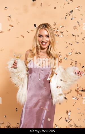 Heureux femme en blanc manteau en fausse fourrure avec cocktail debout sous la chute d'argent confettis sur fond beige Banque D'Images