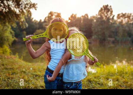 Les petites filles s'amuser en plein air après jouer au badminton. Sœurs couvrir visages avec raquettes en été Parc. Les enfants. Journée internationale de Childrens