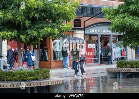 Un couple s'abriter de la pluie sous un parapluie tout en passant devant les vitrines des magasins dans un centre commercial