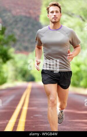 Homme qui court sur la route. Sport et fitness marathon runner pour la formation d'entraînement fait l'extérieur en été. Modèle sport athlète masculin en bonne santé et leurs aspirations. Banque D'Images