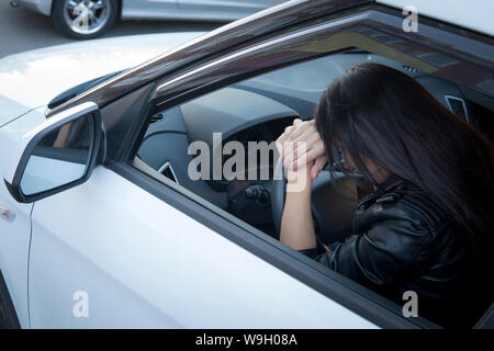 Afficher la fenêtre d'un formulaire/stressé ou fatigué fille brune en location situé sur le volant. La pilote se reposant dans véhicule. Jeune fille se sentait fatigué Banque D'Images