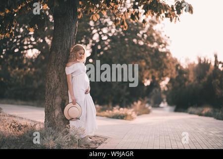Belle femme enceinte de 20 à 24 ans debout dans parc au cours de la lumière du soleil. Robe blanche et élégante portant holding Straw Hat à l'extérieur. La maternité. Mater Banque D'Images
