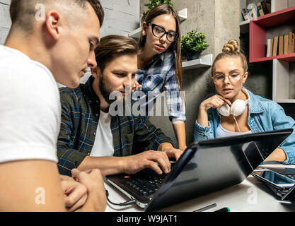 Inspiré de jeunes cols blancs regarder partenaire de bureau travaillant dans un bureau loft Banque D'Images