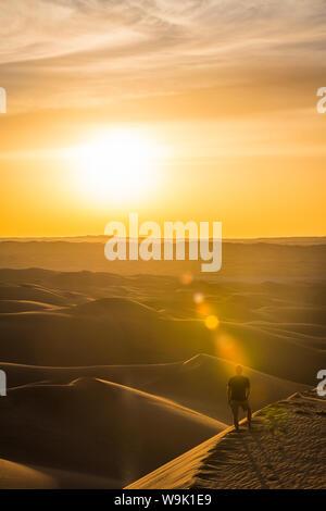 L'homme pour le coucher du soleil dans les dunes de sable géantes du désert du Sahara, Timimoun, dans l'ouest de l'Algérie, l'Afrique du Nord, Afrique