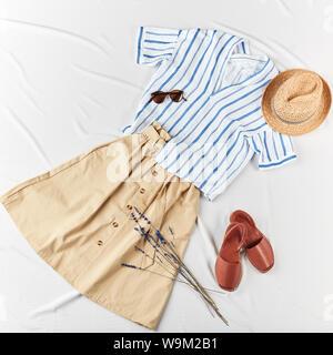 Stried, chemise blanche, jupe marron chapeau canotier de paille, chapeau de paille, sur fond blanc. La femme tenue décontractée. Mise à plat, vue du dessus. Simple Mode look minimaliste de base. Banque D'Images