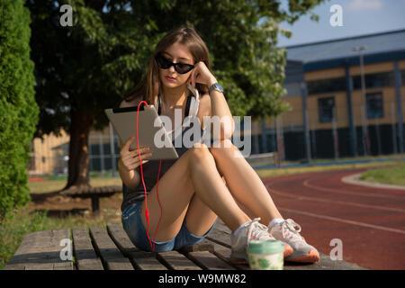 Jolie jeune fille lecture ebook sur une tablette numérique sur un banc dans le parc sur une journée ensoleillée dans le coucher du soleil. Girl porte des lunettes et des écouteurs Banque D'Images
