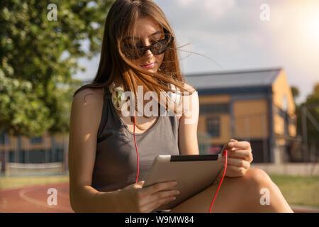 Cute girl with digital tablet computer et le vent dans les cheveux lisant sur un banc dans le parc sur une journée ensoleillée dans le coucher du soleil. Girl porte des lunettes Banque D'Images