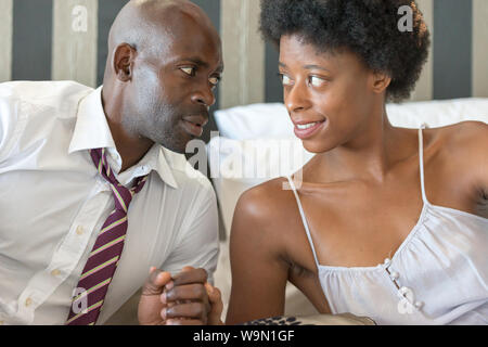 Nam africains et femme couple allongée dans son lit, à la recherche dans les yeux de façon romantique Banque D'Images