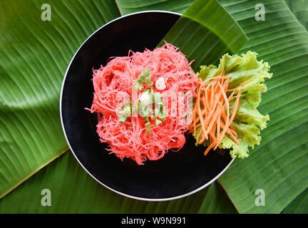 Les vermicelles de riz et légumes frire rose / nouilles de riz sautées avec sauce rouge servi sur plaque sur banana feaf , Nouilles Thai style Asiatique Banque D'Images