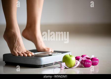 Jambe femme marchant sur des balances avec ruban à mesurer, d'haltère rose et vert pomme. Mode de vie sain, de l'alimentation et du sport concept. Banque D'Images