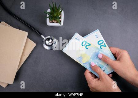 Femme euro argent en mains. Livres et stéthoscope sur table béton Banque D'Images