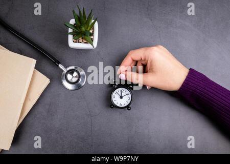 Main de femme est titulaire d'un réveil. Livres et stéthoscope sur table béton Banque D'Images