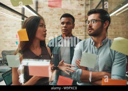 Carte Kanban. Joyeux collègues masculins et féminins de travail Planification et processus à l'aide d'autocollants colorés tout en se tenant en face de mur en verre. Le travail d'équipe. Gestion de projet