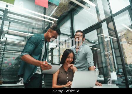 Heureux de travailler ensemble. Groupe de trois jeunes employés et positive à l'aide de technologies modernes et souriant tout en travaillant dans un bureau moderne. Concept d'emploi. Lieu de travail Banque D'Images