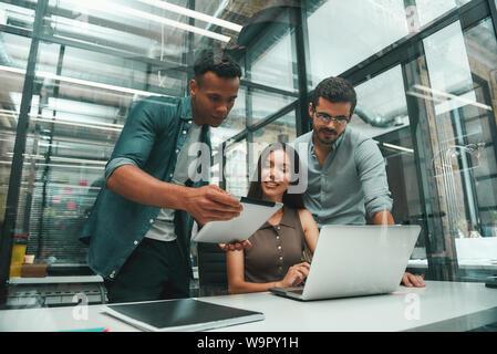 La recherche de solutions. Groupe de trois jeunes employés et positive à l'aide de technologies modernes et de discuter d'une chose tout en travaillant dans un bureau moderne. Concept d'emploi. Lieu de travail Banque D'Images