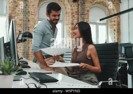 Les professionnels. Belle jeune femme montrant certains documents à son collègue masculin gaie et de discuter des résultats du projet tout en travaillant ensemble dans un bureau moderne. Les gens d'affaires. Lieu de travail Banque D'Images