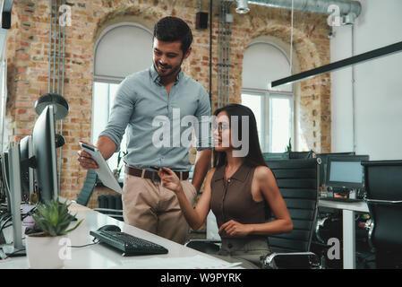 Nous avons de grands résultats jeunes bel homme dans les tenues montrant quelque chose de sa tablette numérique à sa belle femme à un collègue dans un bureau moderne. Lieu de travail. Concept d'entreprise. Banque D'Images