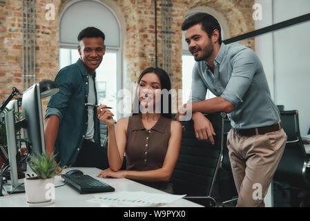 Atmosphère positive. Belle jeune femme pointant à l'écran d'ordinateur et de discuter de nouveau projet avec ses collègues tout en restant assis dans un bureau moderne. Les gens d'affaires. Lieu de travail Banque D'Images