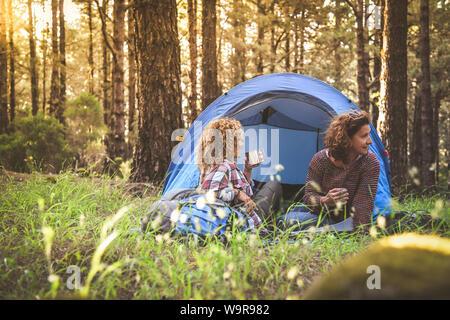 Couple de jeunes femmes à la mode de boire du café et du thé assis dans une tente de camping Trendy sporty girls se détendre dans la forêt après un tour de randonnée