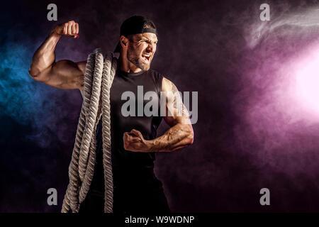 Athletic barbu à bodybulder bataille holding rope sur arrière-plan foncé. la fumée avec studio La force et la motivation. Banque D'Images