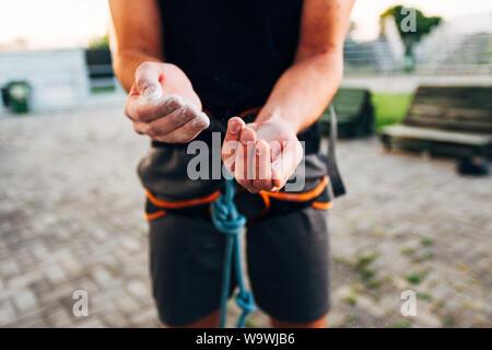 Homme grimpeur dans ses mains de revêtement en poudre de magnésium et de craie prépare à grimper Banque D'Images