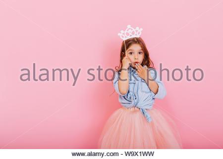 Surpris jeune fille souriante à tulle jupe avec couronne sur la tête exprimant isolé sur fond rose. Amazing cute little princess au carnaval. Place pour le texte Banque D'Images