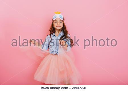 Jolie jeune fille joyeuse avec de longs cheveux de brunette en danse jupe en tulle isolé sur fond rose. Amazing cute little princess avec masque sur la tête, souriant à la caméra de positivité exprimant Banque D'Images