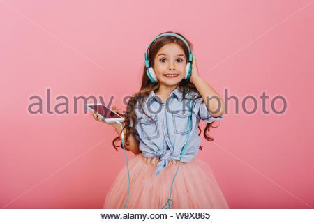 L'expression de positivité de l'enfant heureux d'écouter de la musique via un casque bleu isolé sur fond rose. Jolie petite fille avec de longs cheveux de brunette smiling to camera à tulle jupe Banque D'Images