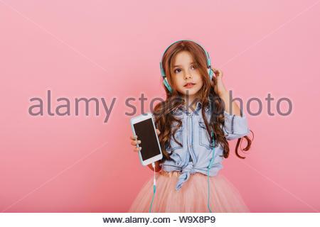 Belle petite fille avec de longs cheveux de brunette avec le téléphone à l'écoute de la musique via un casque bleu isolé sur fond rose. L'humeur joyeuse de jeune enfant, écouter de la musique Banque D'Images