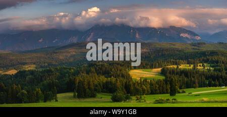 Panorama des Tatras. Des pics de montagne dominant les collines d'herbe verte. Au-dessus des sommets, de beaux nuages de tempête illuminée par le paramètre s Banque D'Images