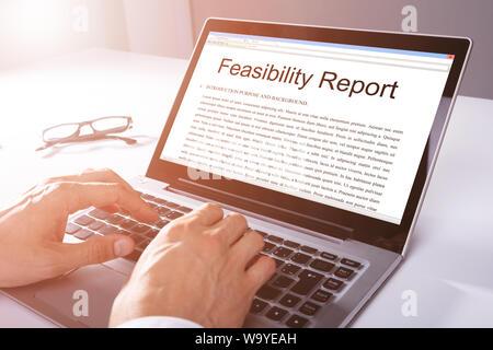 Man Typing On Laptop avec rapport de faisabilité sur écran dans Office Banque D'Images