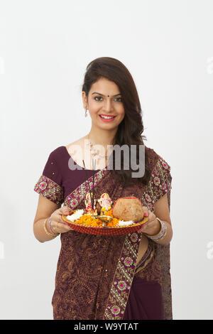 Woman holding pooja thali et souriant
