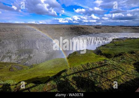 Photo aérienne d'une cascade au milieu des falaises et un arc-en-ciel