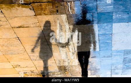 Réflexion floue des silhouettes d'ombre d'un jeune couple en train de marcher sur une rue humide sur une journée ensoleillée dans la vieille ville de chaussée de pierre Banque D'Images