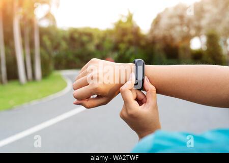 Femme fitness runner Configuration de Smart watch avant l'exécution. Les activités de l'exercice en plein air Banque D'Images