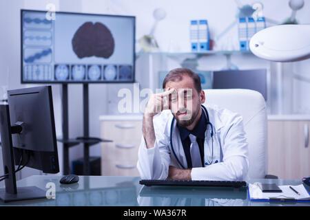 Portrait de jeune scientifique surchargé dans le laboratoire de l'hôpital. Médecin ayant un mal de tête après une longue journée à l'hôpital. Banque D'Images
