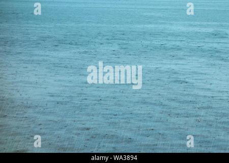 Surface de l'eau avec des gouttes et des ondulations. Lac ou étang d'arrière-plan de pluie Banque D'Images