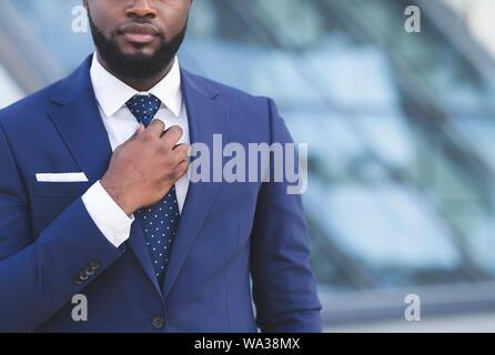 Black Businessman Adjusting Necktie balade en ville, Cropped Banque D'Images