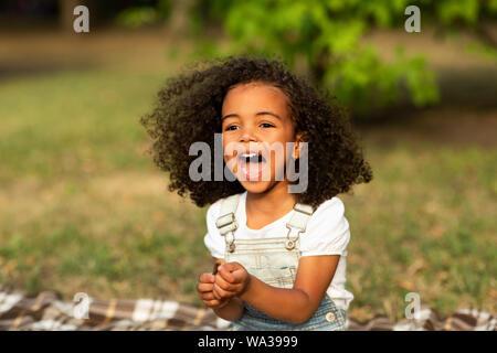 Rire petite fille assise sur la couverture sur l'herbe, se reposer à l'extérieur Banque D'Images