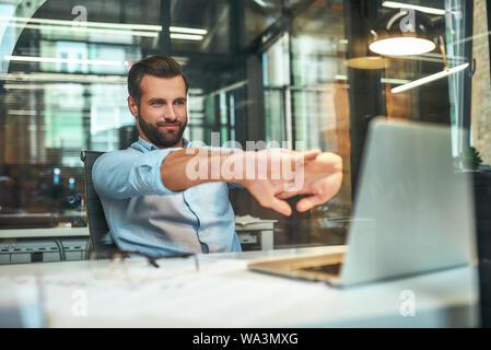 Pas de stress. Jeune homme barbu dans l'usure formelle s'étend ses bras et souriant tout en étant assis dans les bureaux modernes. Lieu de travail. Faire une pause Banque D'Images