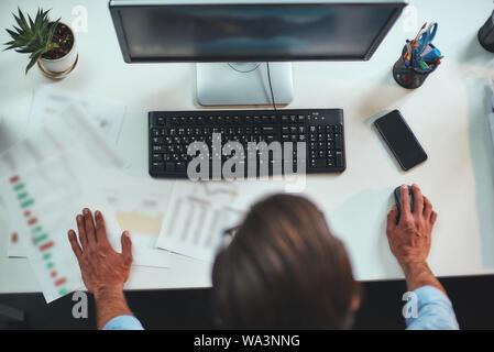 Dure journée de travail. Vue de dessus d'un homme d'affaires travaillant à l'ordinateur tout en se tenant dans le bureau. Concept d'entreprise. Lieu de travail Banque D'Images