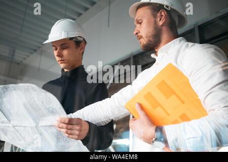 Travailleur du bâtiment et l'architecte discuter construire dessin sur chantier de construction. Deux ingénieurs industriels portant casque ont réunion sur commerci
