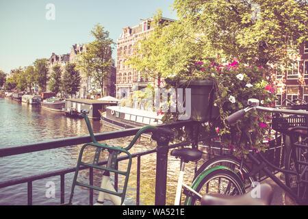 Amsterdam avec des vélos sur le pont sur un canal avec filtre de tonalité vintage.