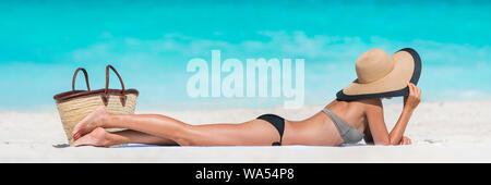 Vacances d'été plage soleil détente femme sur le sable blanc des Caraïbes et l'océan turquoise. Jeune fille touristiques allongé sur une serviette par mer wearing bikini et sun hat bénéficiant d'été voyage vacances. Banque D'Images