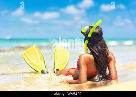 Beach Vacation tuba tuba girl avec masque et palmes. Bikini woman relaxing on été couchés dans l'eau après la plongée avec tuba tuba et palmes pour bronzer. Banque D'Images
